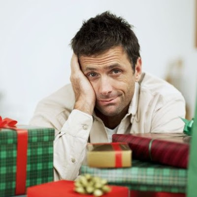 mid adult man sitting confused amidst a pile of wrapped gifts